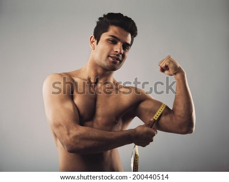 Fit hispanic male model measuring his body. Masculine young male measuring biceps with tape measure on grey background.
