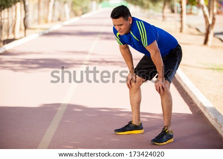 Fit Hispanic runner stopping for a moment to get some air after a long run - stock photo