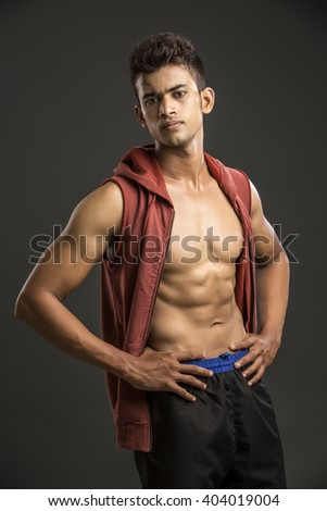 Fit Indian muscular young man posing over dark background. - stock photo