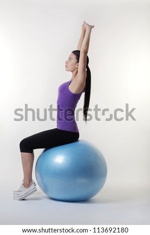 fit looking young woman doing stretching exercises on a gym ball - stock photo
