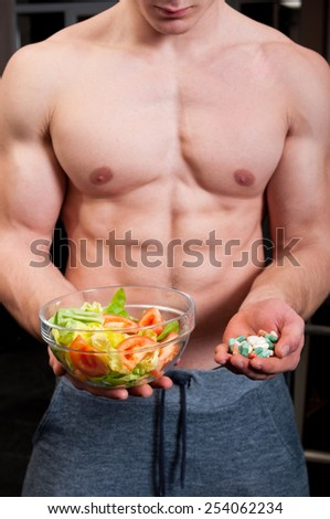 Fit male chosing between bunch of various pills and natural salad - stock photo