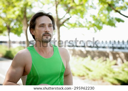 Fit male runner training for marathon. Running fitness man sprinting outdoors in beautiful private garden on his own.