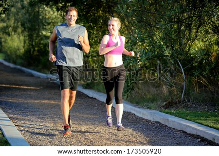 Fit man and woman running together - stock photo