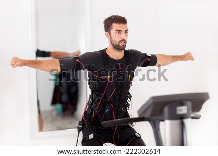 fit man exercise on  electro muscular stimulation machine - stock photo