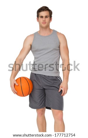 Fit man holding basketball on white background