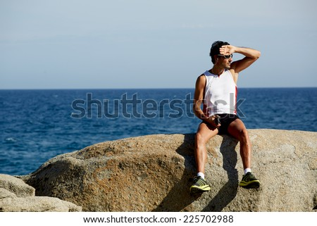 Fit man in bright sportswear taking break sitting on rocks with sea horizon on background, exhausted runner after workout resting seated on big rocks,sportsman listening to music on mobile smart phone - stock photo