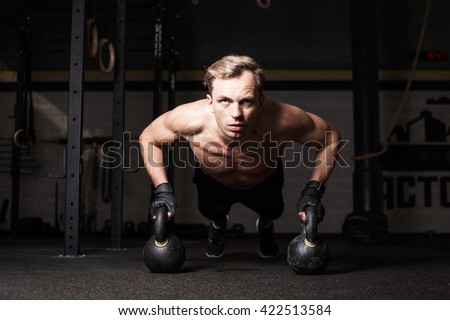 Fit man in gym doing push-ups - stock photo