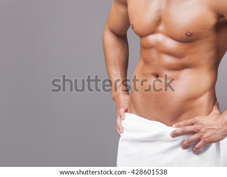 Fit man in towel on grey background - stock photo