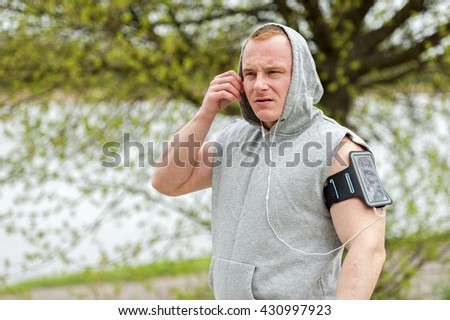 Fit man jogger listening music by earphones.