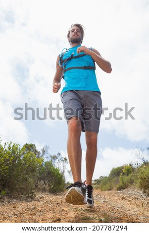 Fit man jogging down mountain trail on a sunny day