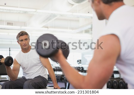 Fit man lifting dumbbells sitting on the bench at the gym - stock photo