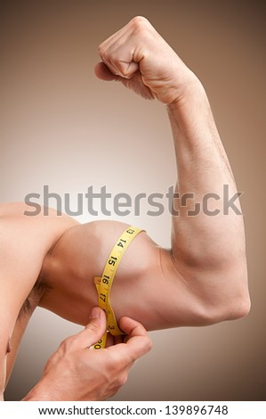 Fit man measures his bicep with a yellow tape - stock photo