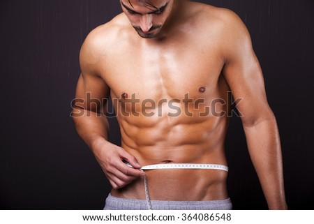 Fit man measuring his waist on grunge background - stock photo