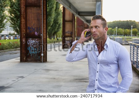 Fit man outdoor in urban environment using cell phone - stock photo