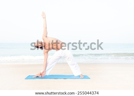 Fit man performing yoga at the beach - stock photo