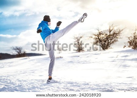 Fit man practicing a kick shot outdoor in snow. Fitness player training and practicing outside on a cold winter day