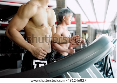 Fit man running on treadmills in fitness