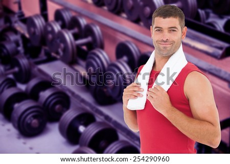 Fit man smiling at camera against collection of barbells - stock photo