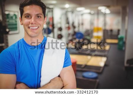 Fit man smiling at camera at the gym - stock photo