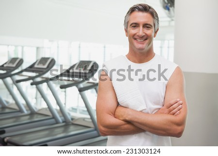 Fit man smiling at camera beside treadmills at the gym - stock photo