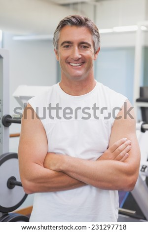 Fit man smiling at camera in fitness studio at the gym - stock photo
