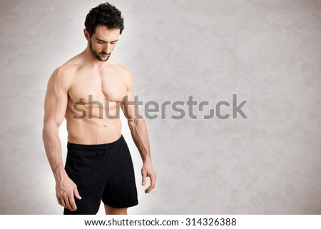Fit man standing shirtless looking down in a grey background