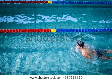 Fit man swimming in the pool - stock photo
