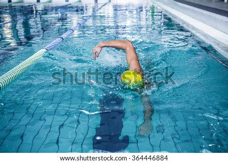 Fit man swimming with swimming hat in swimming pool - stock photo