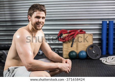 Fit man taking a break from working out at crossfit gym - stock photo