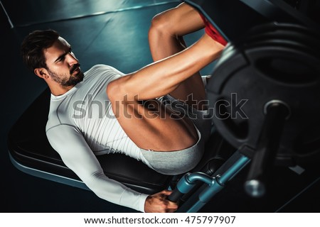 Fit man training legs on leg press machine in the gym