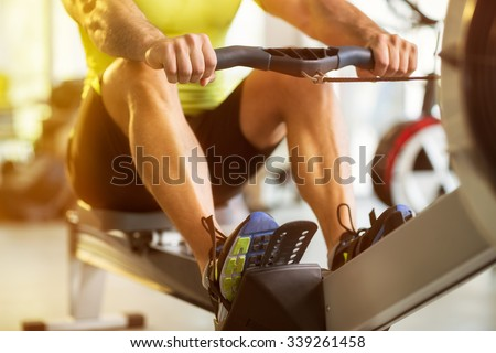Fit man training on row machine in gym - stock photo