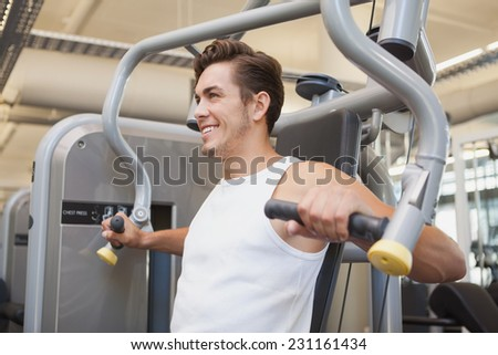 Fit man using weights machine for arms at the gym - stock photo