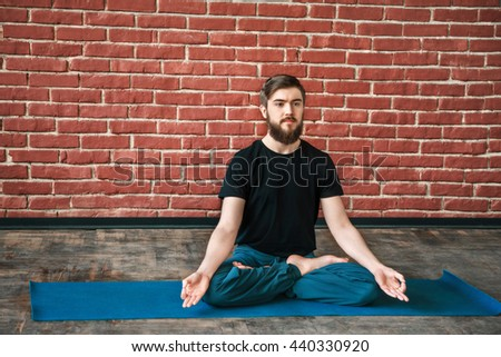 Fit man with a beard wearing black T-shirt and blue trousers doing yoga position on blue matt at wall background, copy space, portrait, lotus asana, padmasana - stock photo