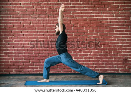 Fit man with a beard wearing black T-shirt and blue trousers doing yoga warrior position on blue matt at wall background, copy space, portrait, virabhadrasana asana. - stock photo