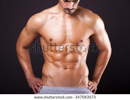 Fit man with beautiful torso on grunge background