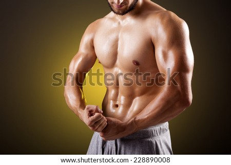 Fit man with beautiful torso posing on dark background - stock photo