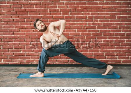 Fit man with dark hair and beard wearing trousers doing yoga position on blue matt at wall background, copy space, portrait, parivritta parshvakonasana asana with namaste mudra - stock photo