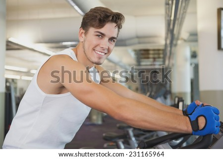 Fit man working out on the exercise bike at the gym - stock photo