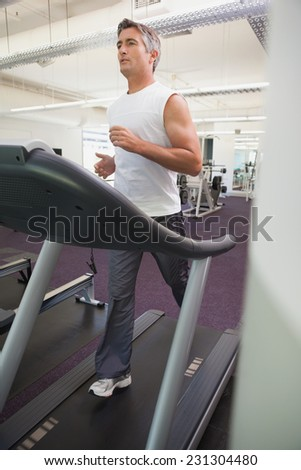 Fit man working out on treadmill at the gym - stock photo