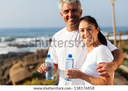 fit mature couple drinking water at the beach after exercise - stock photo