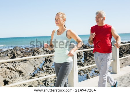 Fit mature couple jogging on the pier on a sunny day - stock photo