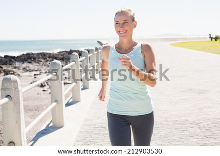 Fit mature woman jogging on the pier on a sunny day - stock photo