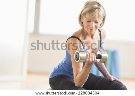 Fit mature woman lifting dumbbell while sitting at home - stock photo