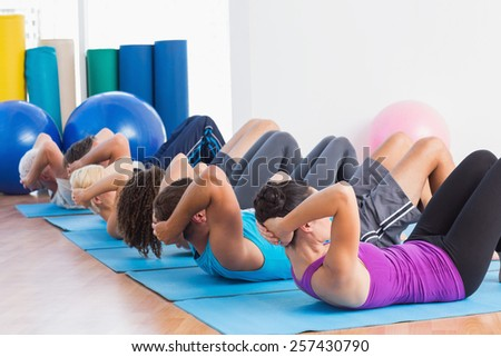 Fit men and women doing sit-ups on exercise mats at fitness club - stock photo