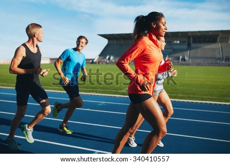 Fit men and women running on a race track. Multiracial athletes practicing on race track in stadium.
