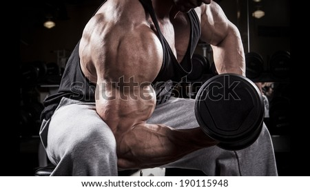 Fit men training his bicep at the gym - stock photo