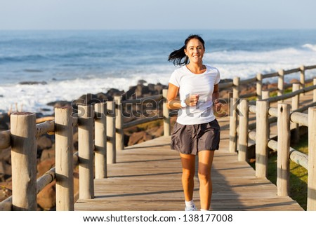 fit mid age woman jogging at the beach in the morning - stock photo
