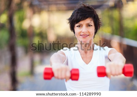 fit middle aged woman exercise with dumbbells outdoors - stock photo