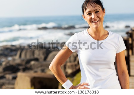 fit middle aged woman portrait at beach in the morning - stock photo