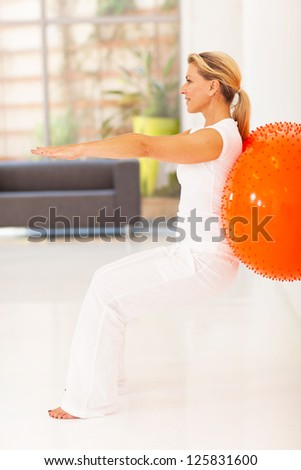 fit middle aged woman workout with exercise ball - stock photo